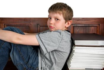 Gefrustreerde jongen zit met zijn rug tegen een stapel boeken