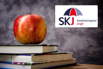 Een stapeltje boeken, een appel én het logo van SKJ Kwaliteitsregister Jeugd voor een schoolbord