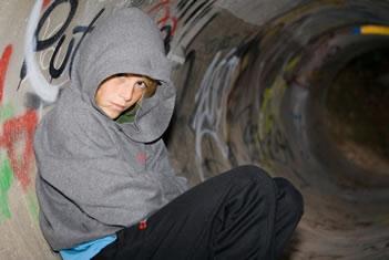 Zittende jongen met capuchon leunend tegen een betonnen wand met graffiti