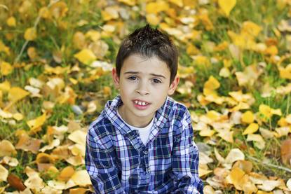 Jongetje in het gras met herfstbladeren