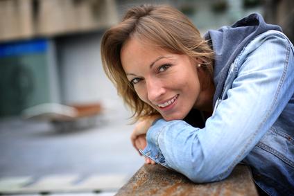 Vrouw met jeansjasje leunt over een reling