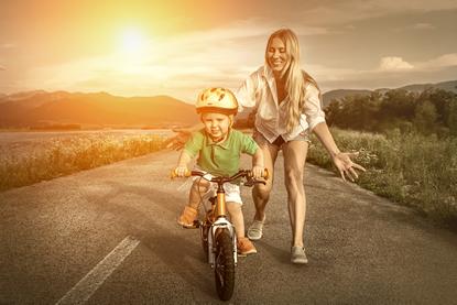 Gelukkige moeder en zoon op de fiets buiten