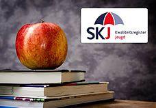 Een appel, een stapel boeken én het logo van SKJ - Kwaliteitsregister Jeugd