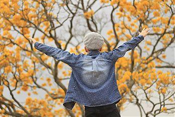 Jongen met pet en spijkerblouse op de rug gezien met armen wijd