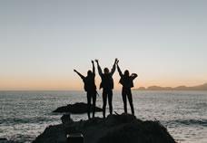Silhouette van drie mensen op een rots aan zee met hun armen in de lucht