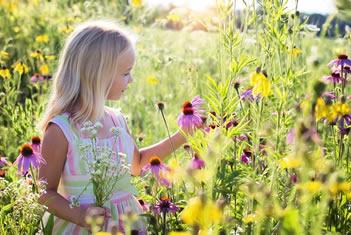 Meisje in een geel en roze bloemenveld