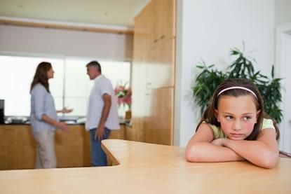 Verdrietig meisje aan tafel, met ouders in conflict op de achtergrond